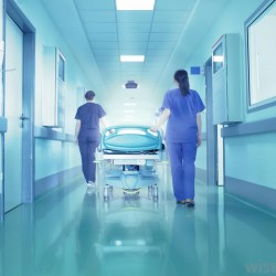 hospital-corridor-with-two-scrubbed-women-pulling-gurney